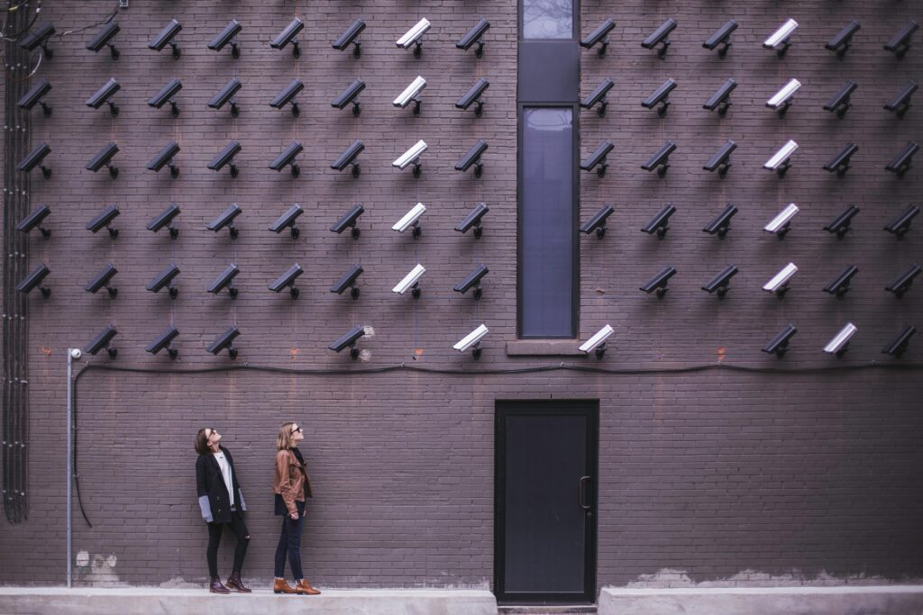 two people standing under security cameras