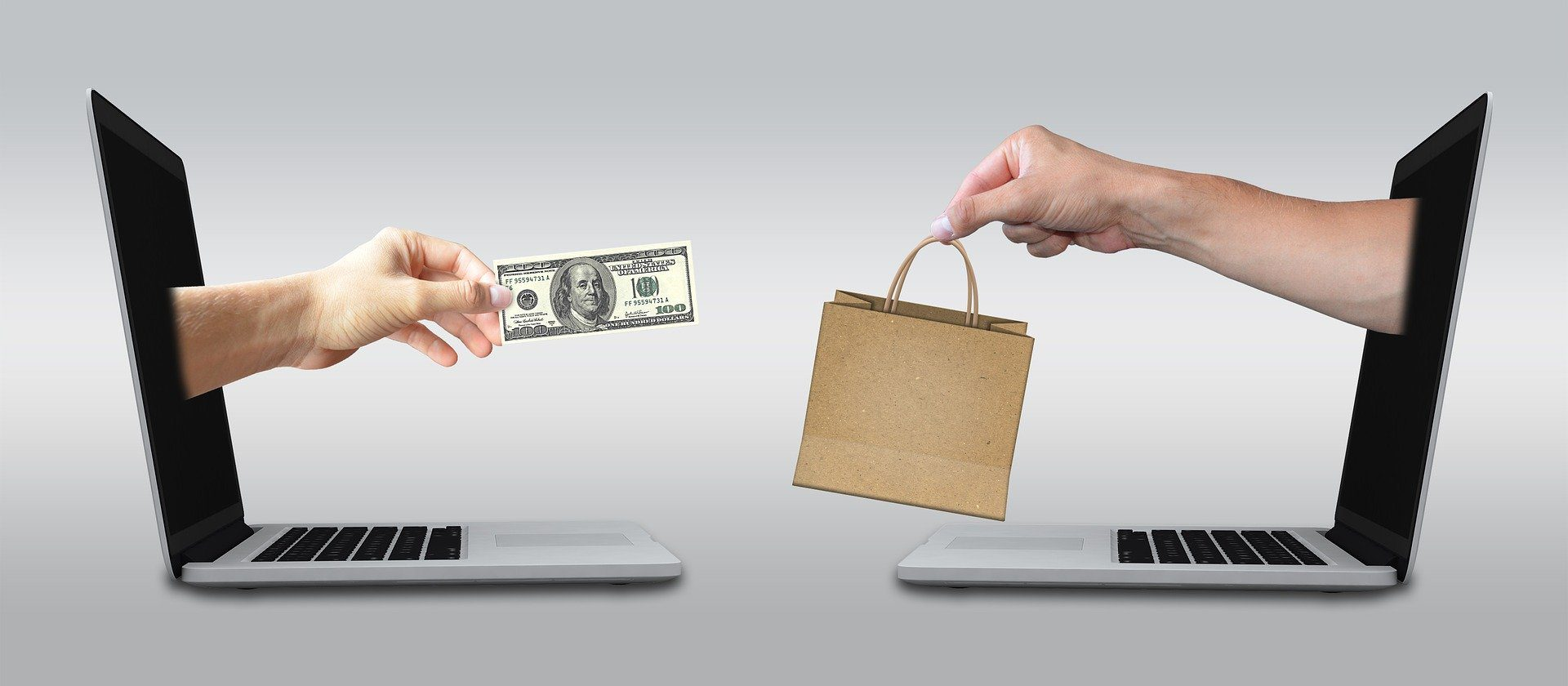 hands reaching out from two laptops exchanging money and a bag