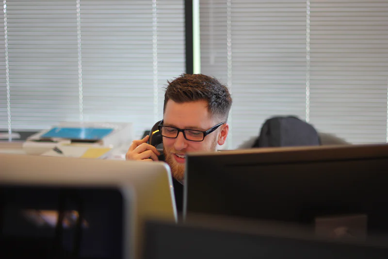 Young man in glasses is speaking on a phone in the office