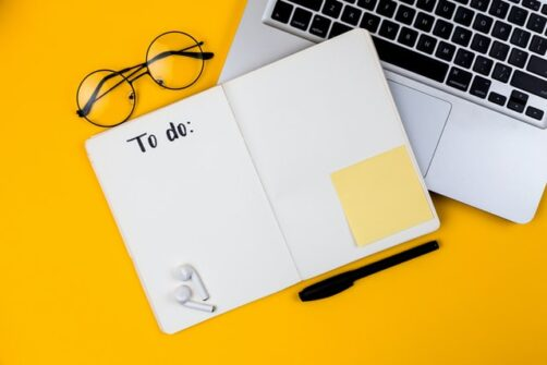 Home office desk workspace with laptop on yellow background